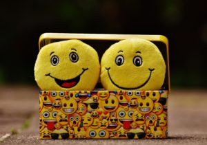 two happy-face emojis in a box of emojis